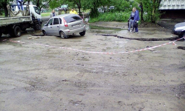 На Левом берегу Омска машины проваливаются в ямы на размытой дороге